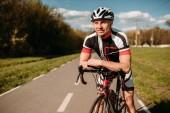 Cyklista v helmě a sportovní oblečení, Cyklistika výcvik na asfaltovou silnici. Samec sportovec jezdí na kole. Cvičení na cyklostezce