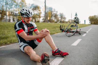 Male bycyclist fell off bike and hit his knee, cycling on bike path. Sportsman rides on bicycle