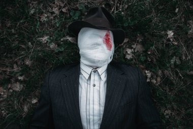 Serial maniac with face wrapped in bloodied bandages lies on the ground in the forest, crazy killer concept, psycho murderer