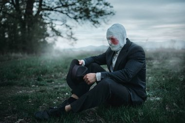 Serial maniac with face wrapped in bloodied bandages sitting on the ground in the forest, crazy killer concept, psycho murderer