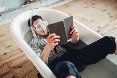 Funny businessman in flippers and mask lies in bathtub and reads book, humor. Business lottery concept