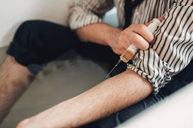 Businessman bankrupt wants to die from a drug overdose, suicide man sitting in bathtub and gives himself a syringe injection. Problem in business, stress