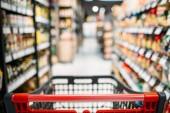 Nákupní košík mezi regály v obchodě potravin, nikdo. Řady výrobků v supermarketu