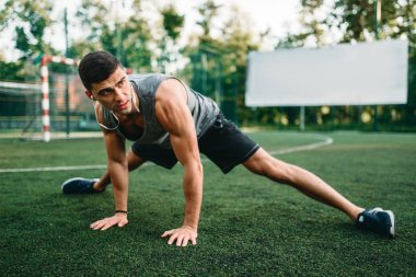 Male athlete on outdoor fitness workout. Sportsman sits on grass and doing stretching exercise