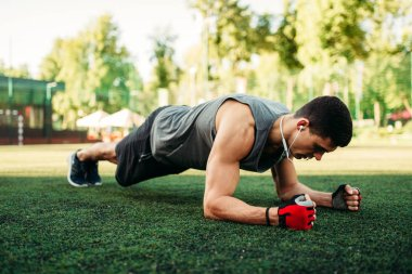 Athletic man doing push-up exercise on a grass, outdoor fitness workout. Muscular sportsman on sport training in summer park