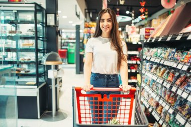 Female customer with cart in food store. Woman shopping in grocery, buyer in market