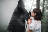 Fotografie Female victim and death in a black hoodie and with a scythe, forest on background. Photo in horror style, exorcism