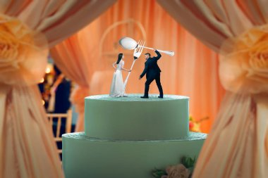 Wedding cake, bride and groom figurines hold huge cutlery in their hands on the top. Bridal pie for newlyweds with little figures, traditional celebration ceremony symbol