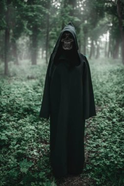 Death in a black hoodie in forest. Horror style, fear, spooky evil