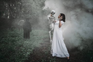 Female victim with human skeleton and death in a black hoodie and with a scythe in the forest. Photo in horror style, exorcism
