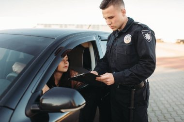 Male cop in uniform checks license of female driver. Law protection, car traffic inspector, safety control job