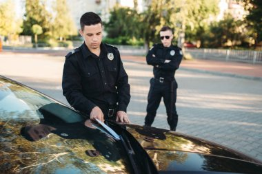 Policemen in uniform writes car fine without a driver. Law protection, vehicle traffic inspector, safety control job