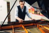 Mužské pianista nastavuje křídlo před vystoupením hudební kompozice. Hudebník upravuje royale, klasické hudební nástroj ladění
