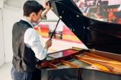 Mužské pianista otevírá víko černé křídlo. Hudebník upravuje royale, klasické hudební nástroj ladění