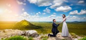 Groom makes the bride a marriage proposal, love couple in an unusual place, green valley on background. Newlywed, newly married couple