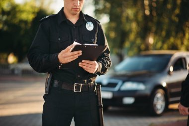 Cop in uniform with notebook in hands check the car on road. Law protection, car traffic inspector, safety control job