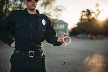 Serious police officer in uniform and sunglasses holds handcuffs, front view. Cop at the work. Law protection concept, safety control job