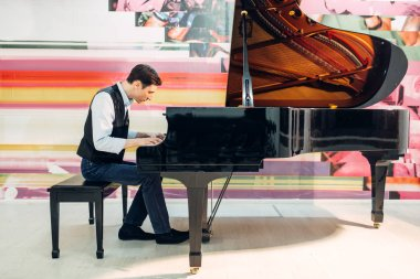 Male pianist practicing composition on grand piano. Musician plays melody at the royale, classical musical instrument