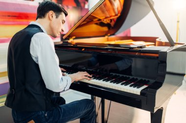 Male pianist at the classical black grand piano, performance in studio. Musician plays melody at the royale keyboard, musical instrument
