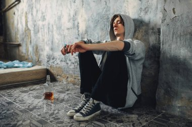 Junkie with syringe in hand sitting on the floor after dose, bottle of alcohol is near. Drug addiction concept, narcotic addicted people