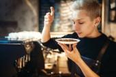 junge männliche Barista schnuppert frische Kaffeebohnen, Cafétheke im Hintergrund. professionelle Zubereitung von Espresso durch Barkeeper in der Cafeteria, Beruf Barkeeper