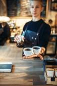 Fotografie Junge männliche Barista in schwarz Schürze hält in Händen zwei Tassen frischen Kaffee, Café Zähler auf Hintergrund. Professionelle Espressozubereitung Barmann in Kantine, Barkeeper Besetzung