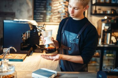 Young male barista makes fresh espresso at cafe counter. Barman works in cafeteria, bartender prepares black coffee