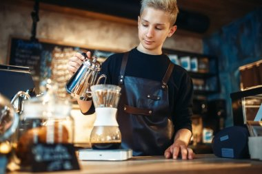 Young male barista makes latte, cafe counter and espresso machine on background. Barman works in cafeteria, bartender prepares coffee