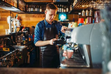 Male bartender prepares drink at the bar counter. Barkeeper occupation, barman working in pub