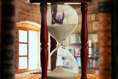 Man drowning inside an hourglass, deadline concept, bookshelf in the office on background