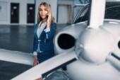 Fotografia Attraente hostess in uniforme pose contro piccolo aeroplano in hangar. Assistente di volo in vestito vicino aereo. Compagnia aerea privata, Assistente di volo