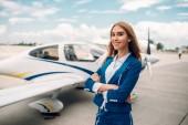 Fényképek Mosolyogva stewardess a kis repülőgép elleni egységes jelent. Légi hostess ruha sík közelében. Magán légitársaság, légi utaskísérő