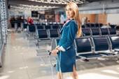 Fényképek Szexi stewardess bőrönddel, repülőtéri váróteremben. Légi hostess ruha csomagokkal, légiutas-kísérő foglalkozás
