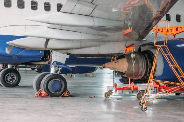 Passenger jet airplane in hangar, plane on inspection before flight. Aircraft on repairing, fixing the problem, engine maintenance, troubleshooting, air transportation safety