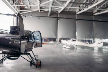 Private airline air park in airport hangar, small turboprop airplane and helicopter in aerodrome building, propeller plane and copter, inspection before flight.Business air transportation or aeroclub