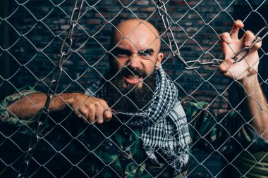 Bearded violent terrorist with knife against metal grid, male mojahed. Terrorism and terror, soldier in khaki camouflage, brick wall on background