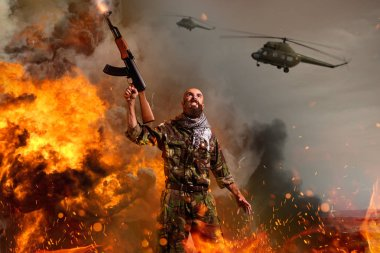 Bearded terrorist with rifle in hands stands in explosion and fire. Terrorism and terror, soldier in khaki camouflage, military helicopters in the sky on background