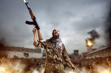 Bearded terrorist with rifle in hands stands in explosion and fire. Terrorism and terror, soldier in khaki camo