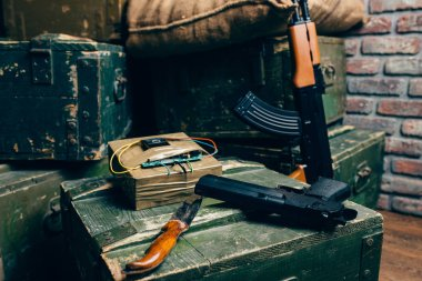Bomb, knife, gun and kalashnikov rifle on box of ammunition, nobody. Terrorism and terror horror concept. Mojahed kit