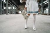 Niedlichen Anime Stil blonde Frau mit Teddy bear in der hand. Cosplay, japanische Kultur, Puppe im Kleid auf verlassenen Fabrik