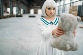 Anime style blonde woman looks at the teddy bear. Cosplay girl, Japanese culture, doll in dress on abandoned factory