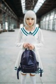 Anime style blonde woman with backpack. Cosplay, japanese culture, doll in dress at abandoned factory