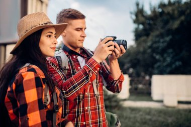 Hikers with backpacks go sightseeing in tourist town and makes photo for memory. Summer hiking. Hike adventure of young man and woman