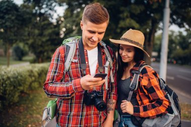 Couple of tourists looking for city attractions on navigator, excursion in  town. Summer hiking. Hike adventure of young man and woman
