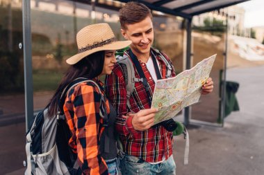Couple at bus stop study the map of city attractions, excursion in tourist town. Summer hiking. Hike adventure of young man and woman