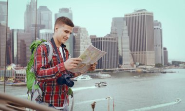 Male tourist with backpack study the map of city attractions, excursion in town. Summer hiking. Hike adventure of young man