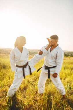 Female karate doing stretching exercise on training with male instructor. Martial art workout outdoor, technique practice, self defense