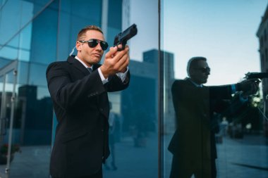 Bodyguard in suit and sunglasses with security earpiece and gun in his hands. Guarding is a risky profession, politicians and business persons protection from the danger of life