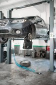 Car with removed wheel on the lift, nobody. Automobile repair, vehicle maintenance, tire service