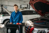 Photo Mechanic stands at the air conditioning diagnostic system. Conditioner inspection in car service